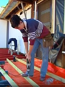 Screenshot of SBS The Feed video showing young woman in a rugby top using a drill on a residential building site.
