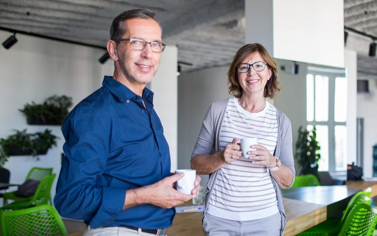 Man and woman drinking coffee in an office and looking at the camera.