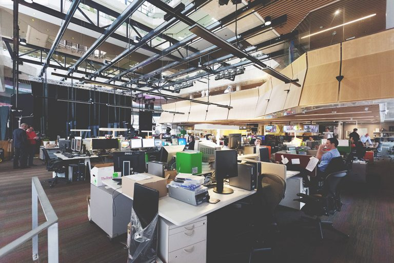 A near empty newsroom with messy desks, a few people working, a television set in the background