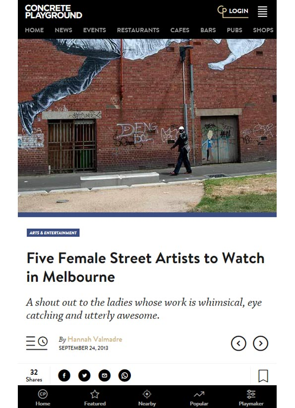 Screenshot of article showing an image of a person walking along a lane by a tall, industrial brick wall with large paste up art on it.