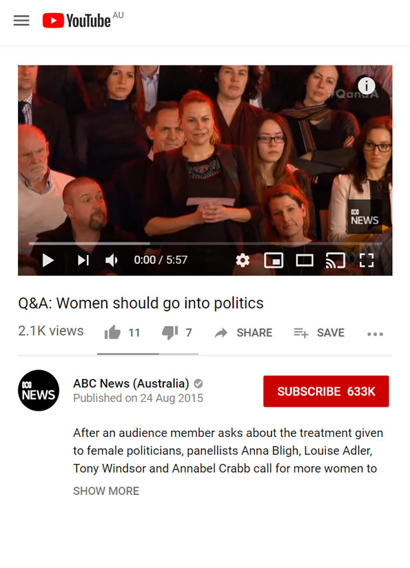 Video still of woman standing up in tv studio crowd, asking a question.