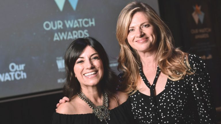 Two public figures Angela Pippos and Julie Zemiro stand close together in front of a projector screen with the Our Watch Awards logo displayed. They are both looking at the camera and smiling.
