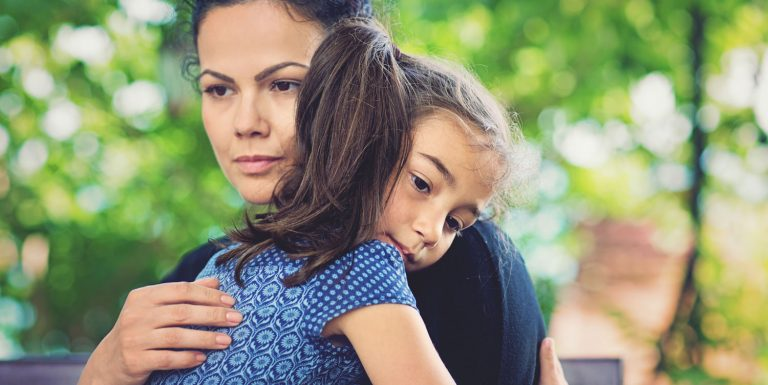 A dark haired woman and a girl embrace each other. There is a greenery in the background.