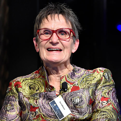 Image of Sue Salthouse. She is wearing a colourful blazer, has short dark hair and red glasses.