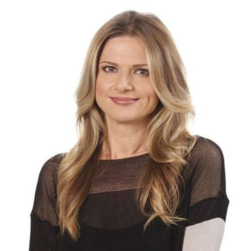 Portrait of Julia Zemiro, who wears a black top and is looking at the camera faintly smiling. She has long light brown hair.