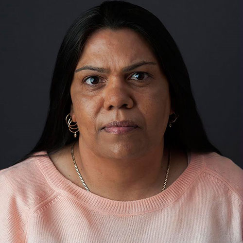 A woman with black hair and silver earrings looking at the camera. She has a light orange top on.