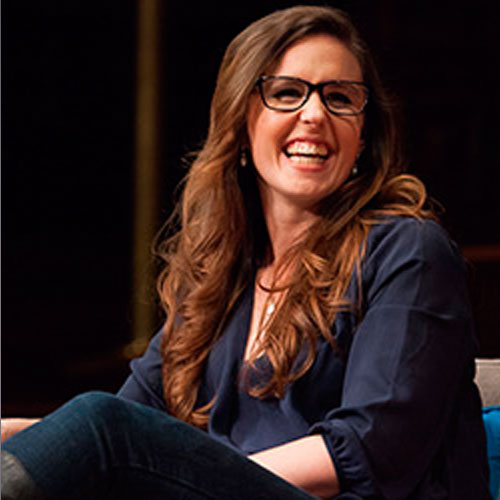 Photo of Drisana Drisana Levitzke-Gray sitting and smiling over her shoulder. She has long brown hair and black glasses and is sitting on a panel.