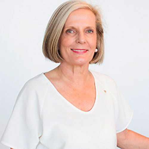 Portrait of Lucy Turnbull. She has medium length white hair and is wearing a white top. She is smiling at the camera.