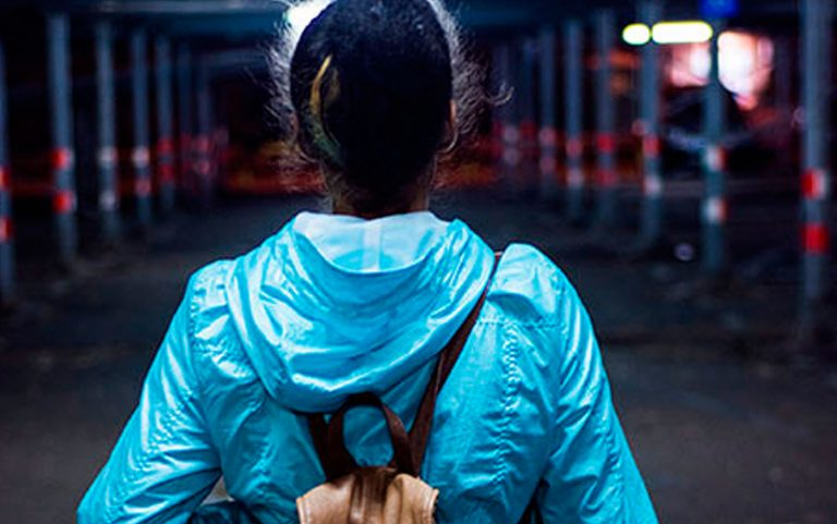 A young woman with tied up dark hair and blue jacket and backpack, seen from behind. She's looking towards a dark scaffolded area at night. She's standing confidently with her legs apart.
