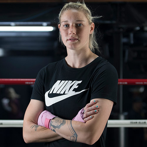 Ambassador Tayla Harris standing in a boxing ring. She is wearing a black t shirt with a logo on it and has her arms crossed in front of her.