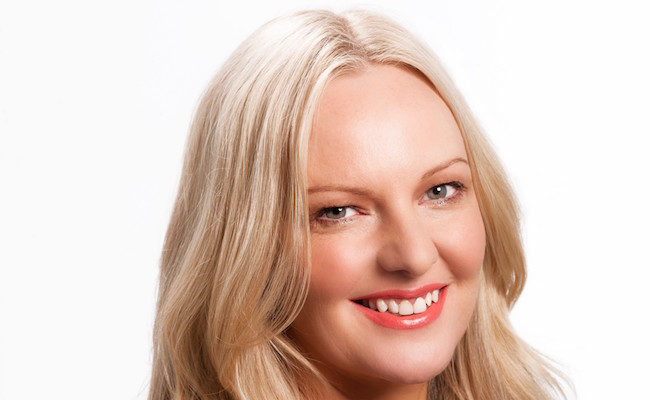 Portrait of Rebecca Poulson. She has long blond hair, is wearing a purple top. She is smiling at the camera.