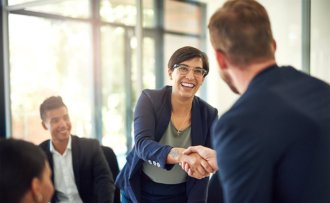 Woman shaking hands with a colleague in an office.