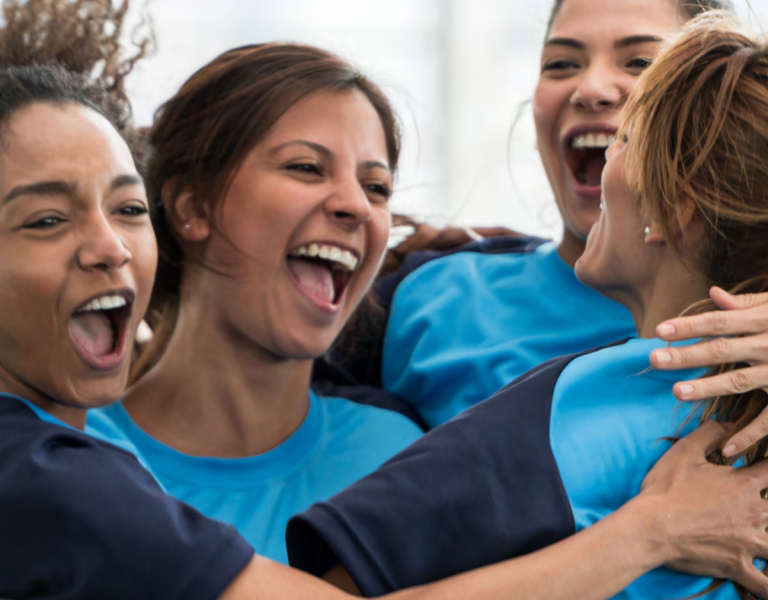 The faces, arms and shoulders of a group of young women standing in a huddle in a team uniform, smiling and cheering