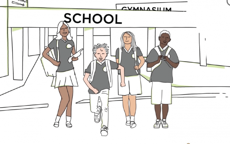 Screenshot of four school aged children in front of their school building.